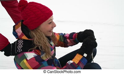 Winter Recreation - Cheerful girl riding a sled, her friend...