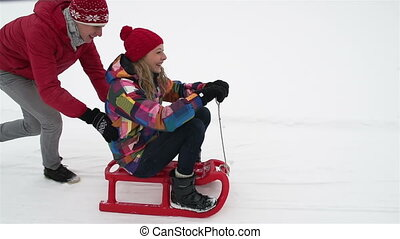 Sledding - Slow-motion of playful friends having an active...