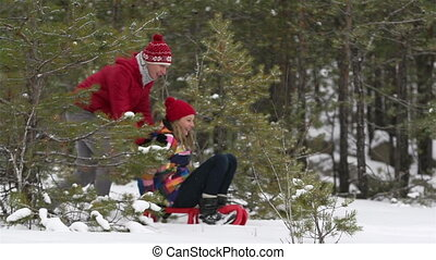 Snowy Ride - Slow-motion of an energetic couple sledding...