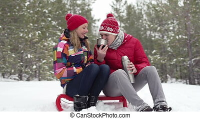 Hot Tea - Young couple sitting outdoors and drinking hot tea...