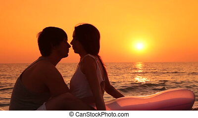 Silhoette of kissing couple on the beach at sunset