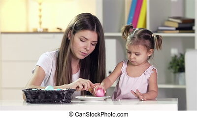 Easter Eggs - Mom and daughter eating colorful boiled eggs