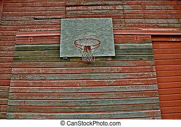 Basketball Hoop on Red Barn Wall - A basketball hoop,...