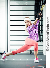 Functional training - Young woman streching muscles...
