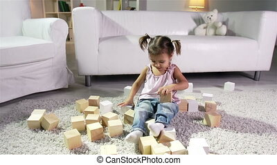 Toy Blocks - Charming girl sitting on the carpet and playing...
