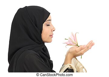 Close up of a profile of an arab woman smelling a flower...