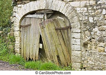 broken door - Stone archway with a derelict door hanging on...