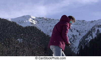 Winter Resort - Young woman throwing snowballs on a...