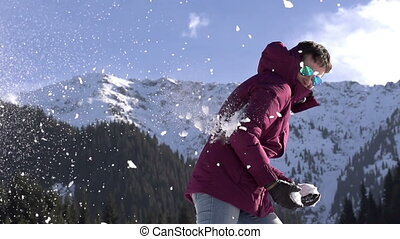 Holiday in the mountains - Young woman throwing snowballs on...