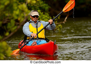 man in kayak in florida - young man in kayak in a tropical...