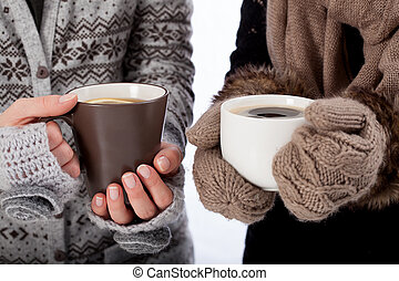 Warming up - Two people holding mugs with hot drinks