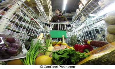 Purchase - Woman with shopping trolley moves on a...