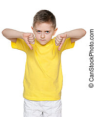 Young boy holds his thumbs down - An upset boy in yellow...