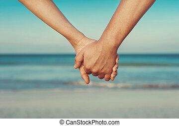 amantes, par, segurando, mãos