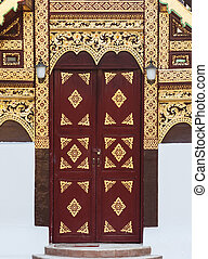 Red and gold Thai style wooden door in temple, Chiang Mai,...