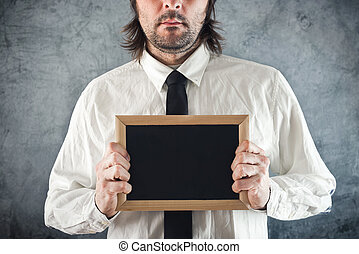 Businessman holding blank blackboard
