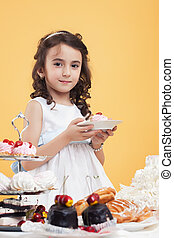 Adorable brown-eyed girl posing with sweets - Adorable...