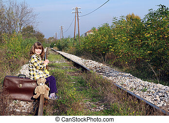 little girl sitting on suitcase and waiting for train