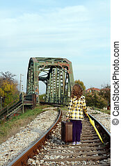 little girl walking on railroad