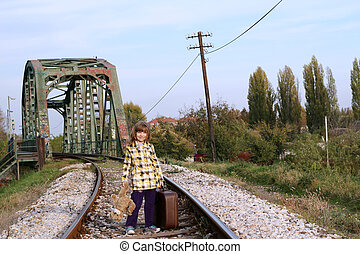 little girl with suitcase and teddy bear standing on railroad