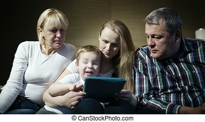 Family watching boy playing game on touchpad