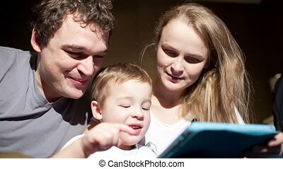 Parents watching son playing game on touchpad - Mother and...
