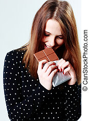 Young beautiful woman eating chocolate on gray background