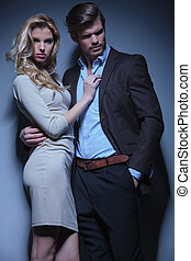 blonde woman embracing her man and posing in studio