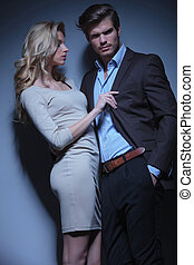 blonde woman pulling her man by his collar against studio...