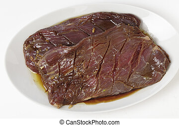 Marinaded flank steak on a plate - Two pieces of marinded...