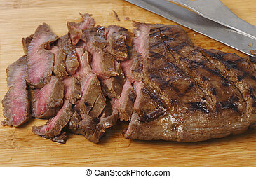 London broil sliced on a board - Marinaded flank steak, or...