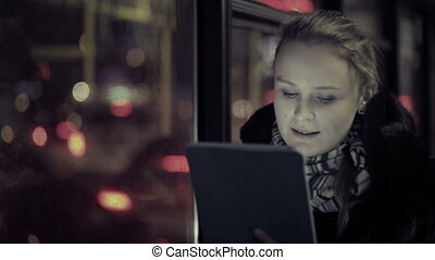 Woman with touchpad in the bus - Young woman watching video...