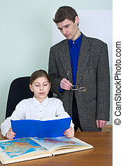 Tutor and schoolgirl with book and atlas