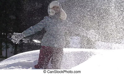 Fluffy Snow - Girl throws fluffy snow on a background of a...
