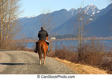 Crisp Winter Day - A man leisurely riding his horse next to...