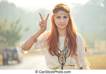 Hippie girl with peace signs in golden field