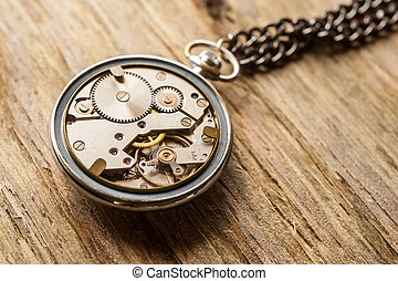 Pocket watch mechanism on wooden background