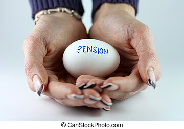 Pension Nest Egg - A womans hands holding an egg with...