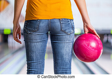 Bowling. Closeup of woman holding a bowling ball focusing for a roll,rear view