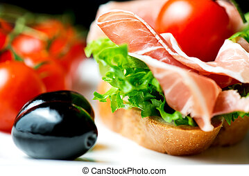 Sandwiches with prosciutto on plate with olive horizontal
