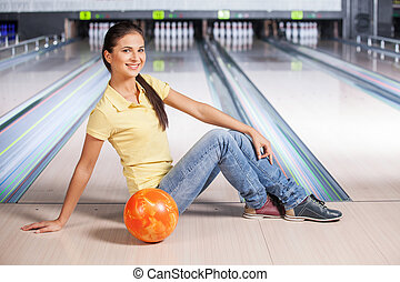Bowling. Young beautiful girl sitting on bowling alley.