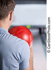 Bowling. Closeup of man holding a bowling ball focusing for a roll,rear view.