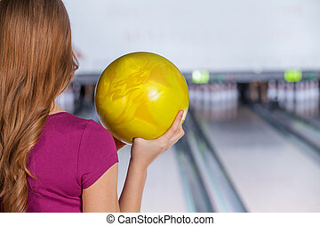 Bowling. Closeup of woman holding a bowling ball focusing for a roll,rear view.