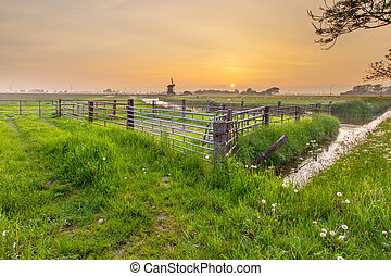 Polder Landscape with Orange Sunset In Groningen, Netherlands