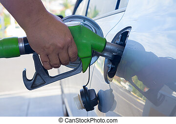 refilling car with fuel - close up of pump refilling car...