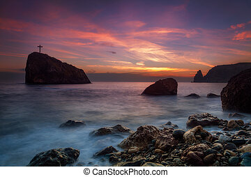 Seacoast at sunset and a cross on a rock