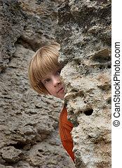 hide and seek - boy playng hide and seek game in the rocks