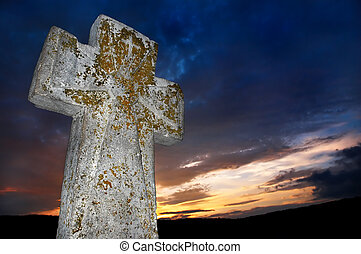 brightly lit stone cross on the sunset background