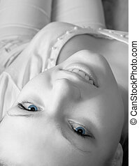 Young glamour woman in white laying on sofa. Grayscale version but blue eyes. High key. Shallow DOF.