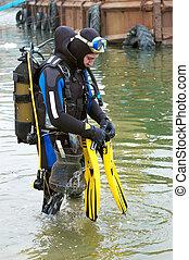 scuba diver entering the water - Scuba diver in wet suit...
